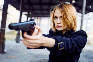 Woman pointing a gun. Mafia girl shooting at someone on the street.