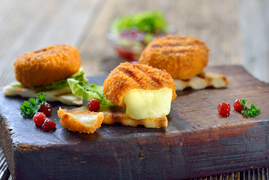 Toast mit heißen Mini-Camemberts und Preiselbeeren -Toasted panini triangles with breaded mini camembert cheese loaves, cranberries and iceberg lettuce served on a wooden cutting board