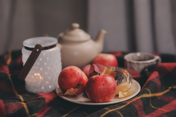 cozy autumn weekend morning at home. Breakfast with cup of tea and bagel with apples on woolen plaid blanket.