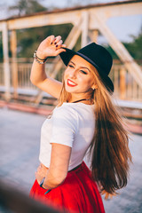 Outdoor lifestyle close up portrait of happy blonde young woman in stylish casual red dress (skirt) and black hat  stay on bridge on the street. Pretty hipster girl having fun and enjoying holidays.