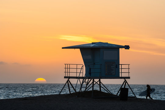 Silhouette of Surfer running past lifeguard tower during sunset on Huntington beach in southern California