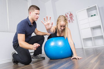 male physio therapist and woman helping patient