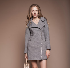 Fashion portrait of glamour young stylish woman wearing trendy coat. Warm clothes. Beige background with copy space