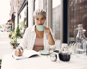 Portrait of woman holding coffee cup and pen at sidewalk cafe