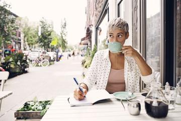 Woman drinking coffee at sidewalk cafe