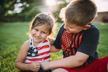 Happy boy tickling sister while sitting at backyard