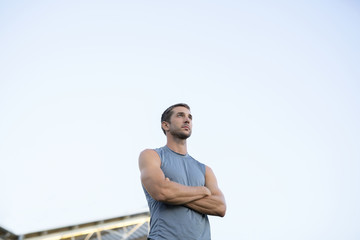 Low angle view of male athlete standing against clear sky