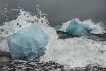 Waves splashing on icebergs in sea