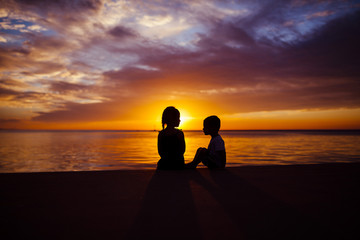 Silhouette siblings sitting by beach during sunset