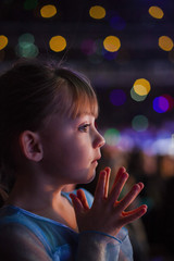 Close-up of thoughtful girl against defocused lights at night