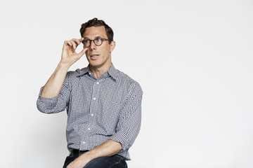 Businessman adjusting eyeglasses while looking away against white wall