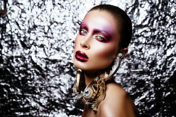 brunette woman in long earrings. high school model with creative make-up