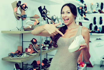 Female customer showing desired shoe in boutique
