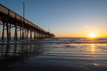 Tide coming in during a beautiful Dramatic Sunset at Newport beach Pier in Orange county, California