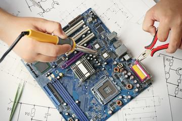 Man using soldering tool for motherboard repair, close up