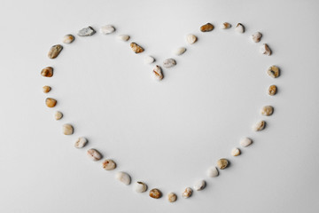 Heart made of small pebbles, isolated on white