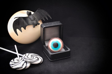 Close up of  a bat against the white moon, candies, gift box with troll eye on traditional black background. Concept for Halloween celebration.Copyspace.