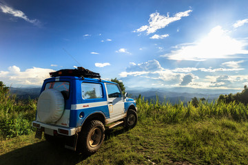 The Blue Off Road car on the top of mountain with blue sky