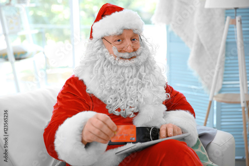 Quot santa claus with credit card and tablet on couch at home