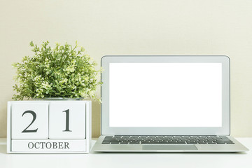 White wooden calendar with black 21 october word with white blank space at center of computer notebook on white wood desk and cream wallpaper textured background , selective focus at the calendar