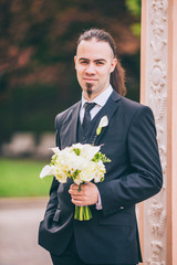 Young stylish man in a suit. Groom with long hair beard and piercing.