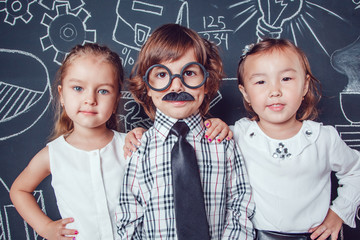 Little boy in glasses and mustache stand on dark background with a pattern. Two girls standing the sides