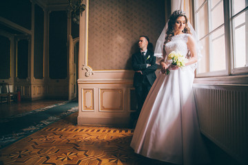 elegant gorgeous bride gently looking under veil at stylish groom standing at window light, holding calla bouquet. unusual wedding couple in retro style