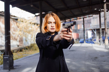 Woman pointing a gun. Mafia girl shooting at someone on the street. Emotion of fear, fright