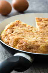 Spanish omelette on frying pan on wooden table