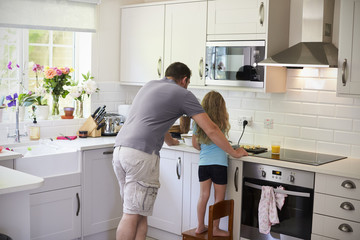 Father And Daughter Making Smoothies In Kitchen Together