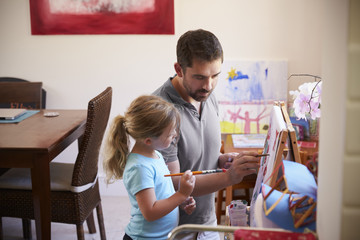 Father And Daughter Painting A Picture At Home Together