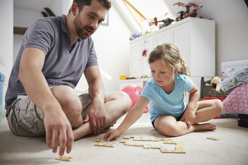 Father And Daughter Playing Dominoes At Home Together