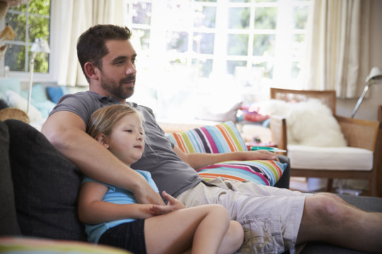 Father And Daughter Sitting On Sofa Watching TV Together