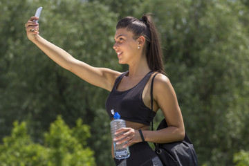 Fitness girl smile and take selfie with mobile phone