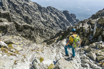 Two hikers descends gully.