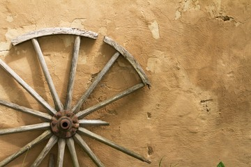 wood, broken wheel leaning against the wall