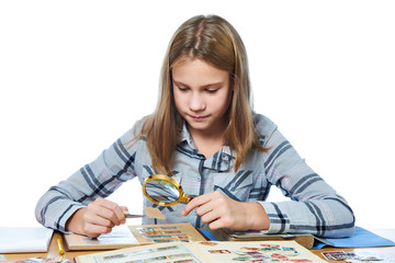 Teen girl with magnifier looks his stamp collection isolated