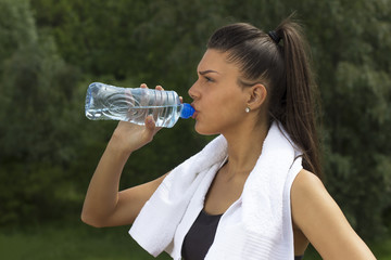 Fitness girl with bottle of water on her hand and towel over her neck