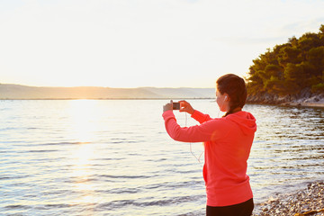 Active young woman listening to music during workout. Runner rests from routine exercise and makes photos. Happy jogger relaxing at the beach after run and looking at the sea. Back view