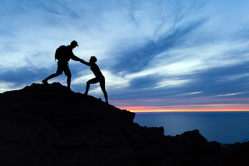 Teamwork couple hikers silhouette in mountains, climbers team