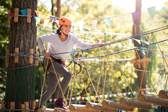 Happy brave woman making a step on the rope ladder
