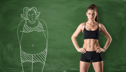 Sporty girl with slim body and drawing of woman on chalkboard