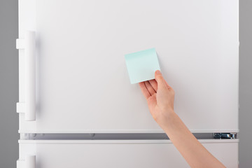 Female hand holding blank blue sticky paper note on refrigerator
