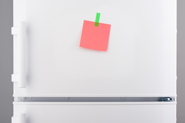 Pink paper note attached with green sticker on refrigerator
