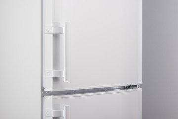 Close up of white refrigerator on gray