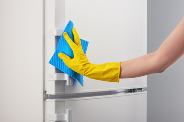 Hand in yellow glove cleaning white refrigerator with blue rag
