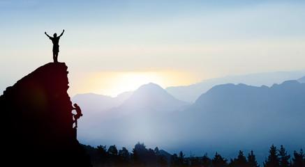 Bergsteiger auf einem Gipfel im Gebirge bei Sonnenaufgang