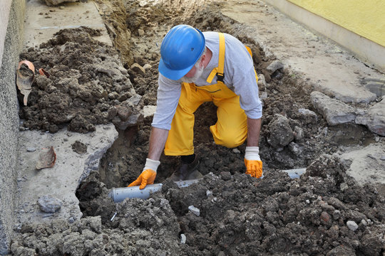 Plumber fixing sewerage pipe at construction site, home renovation