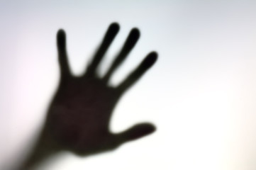 Silhouette of hand on a white surface