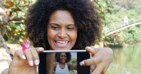 Afro woman taking selfie photos in the park